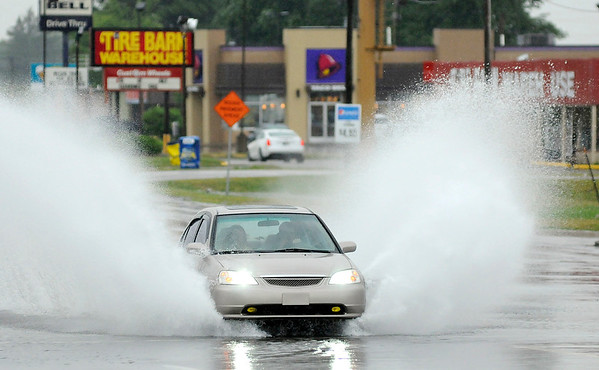 Don Knight | The Herald Bulletin<br /> A motorists drives through the intersection of School Street and Broadway after it was flooded by heavy rains on Friday afternoon. Rain chances remain in the forecast for the weekend.