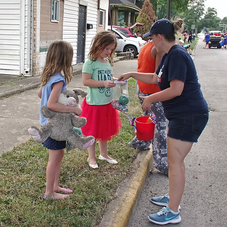 As Emma Romano looks on, her sister, Anastasia, recieves a pencil from a participant in the Ollie Dixon Back to School Parade.(Mark Maynard photo)
