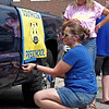 Kimberly Brown and Shelly Simmons attach a banner to the side of their pick-up truck in preparation for the annual Ollie Dixon Back to School Parade on Saturday. (Mark Maynard photo)