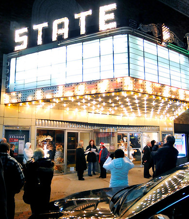 John P. Cleary | The Herald Bulletin   THB file photo<br /> Singers sing Christmas Carols in front of the display windows as people look over the lit up State Theatre marquee Friday evening as part of the downtown holiday festivities.