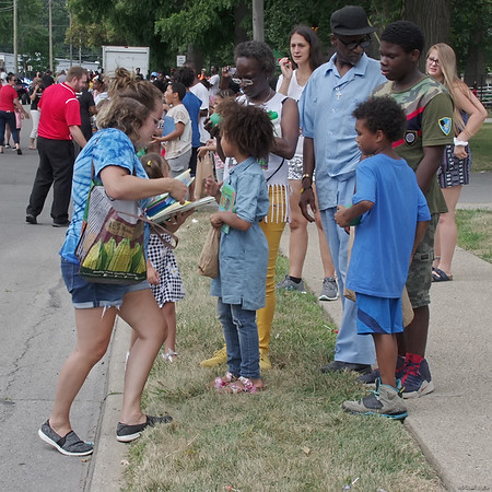 Elizabeth Janes hands out coloring books to spectators during the annual Ollie Dixon Back to School Parade on Saturday. (Mark Maynard photo)