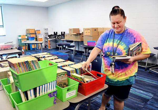 John P. Cleary   The Herald Bulletin<br /> Fifth grader teacher Tami Plummer sorts out books that have been unpacked in her new classroom at Anderson Intermediate School.