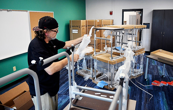 John P. Cleary | The Herald Bulletin<br /> Steve Riddle, of Binford Group, removes the protective packing from new desks as they moved the new furniture into Anderson Intermediate School recently.