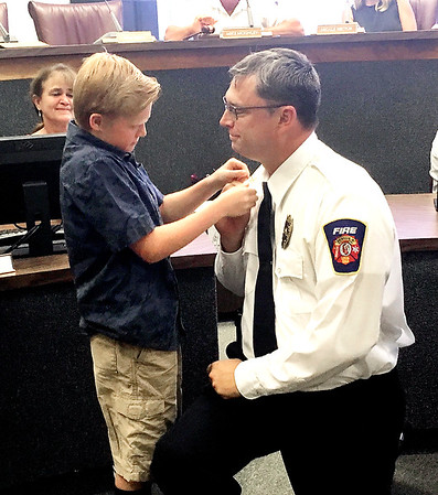Joshua Nodine, 9, pins the chief's bugles to his father, Chris's uniform shirt following his promotion to Chief Arson Firefighter for the Anderson Fire Department.
