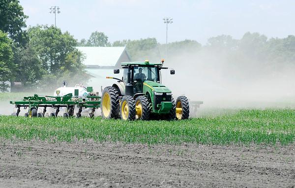 Don Knight | The Herald Bulletin<br /> A farmer fertilizes corn in a field behind Eastside Elementary School on Thursday.