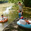 From left, Eric Jarrett and his son Atlas and Phillip Ellingwood his son Kai get in the White River at Walbridge Park in Chesterfield for a float down stream to Anderson on Thursday.