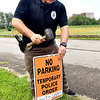 Anderson Police Department officer Joe Heath puts up a No Parking sign along Wilcon Street Thursday, and along the streets that surround Athletic Park, in preparation for the City's July 3th holiday celebration.