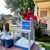 Jerrica Williams volunteers at the Kids Block Party in Anderson on Friday, scooping snow cones for the children.