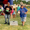 Denny Goodnight, right, tosses a bean bag during a game of cornhole as Shannon Wooden looks on Saturday during Anderson's Independence Day Celebration at Athletic Park.