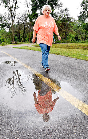 Mary Loy, of Anderson, times her walk around Shadyside Park just right so she could hit that window between rain showers that moved through the area Wednesday morning. Loy was successful in getting her daily walk in, and staying dry.