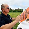 Anderson Police Department officer Joe Heath puts together No Parking signs Thursday to put up along the streets around Athletic Park in preparation for the City's July 3th holiday celebration.
