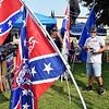 A merchandise vendor, Brad (only gave first name), stands among the flags his has for sale at his booth at the Madison County 4-H Fair Tuesday. Among the items are Confederate flags and political merchandise.
