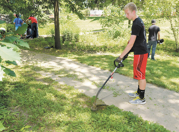 Connor Hall uses a string trimmer to cut down weeds as church youth groups volunteer to clean up Shadyside Park on Thursday as part of Project 765.