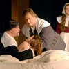 Rev. John Hale (Rick Vale) looks at Betty Parris (Larissa Weber), after falling ill after being discovered dancing and performing pagan rituals, as Rev. Samuel Parris (Greg Simpson) assists as Abigail Williams (Maggie Williams) looks on.