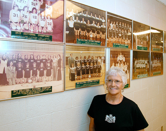 Mary Ruth Rice, former Pendleton Heights High School volleyball coach, in front of photographs of some of her sectional championship teams she coached over the years.