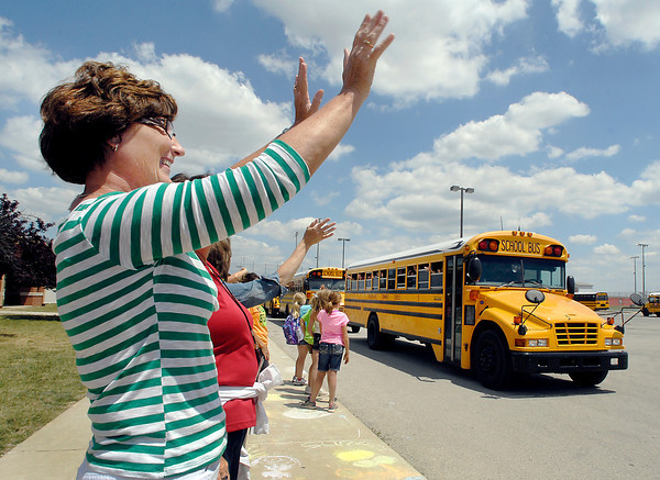Frankton Elementary School music teacher Rhonda Kuntz waves goodbye, along with the entire faculty and staff, to the departing buses at the end of the last day of the school year for the Frankton-Lapel school system.