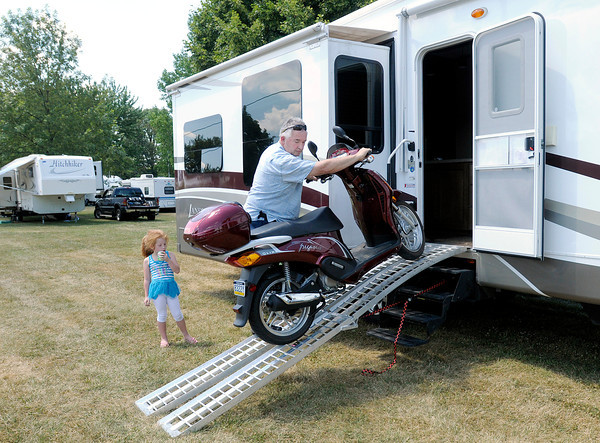 Doug Hoeffner, pastor of Taylor Church of God in Taylor Pa., unloads his scooter from his camper as his granddaughter Rylee Purdy looks on as the Hoeffners set up in the campground for the start of the Church of God Convention.
