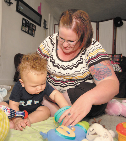 Elizabeth Finley, a college grad with a lot of debt, at home with her son Azir, 7 months.