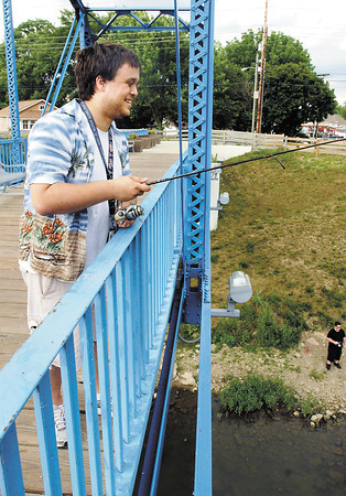 Benjamin Huff tried his luck at fishing off the pedestrian bridge near Edgewater Park Monday evening to hit a spot in the middle of White River.
