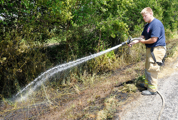 Jordan Allen from the Richland Township Volunteer Fire Department douse the scene of a grass fire on County Road 700 North east of Indiana 9 on Tuesday. Alexandria's fire department made the initial knock down of the fire after conflicting calls first reported the fire at CR 900 North.