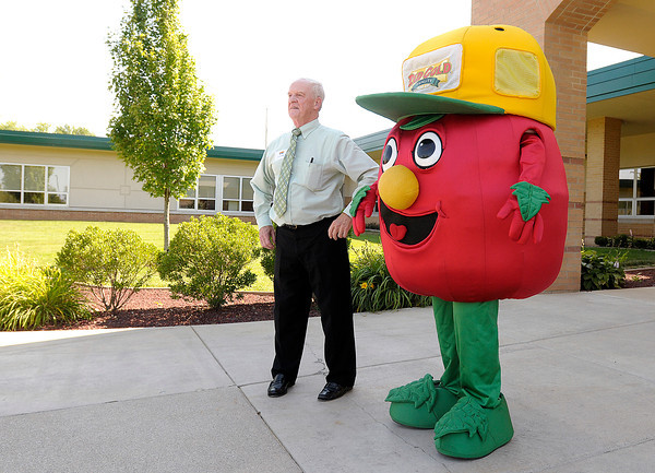 Trevor Kaye and the Red Gold mascot Stewie greet visitors to an open house at Red Gold's new corporate offices in Elwood on Wednesday. Red Gold converted Elwood's former Oakland Elementary School into their corporate offices.