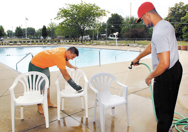 Southside Pool lifeguards Zach Sylvester and Tealgil Stonewall clean deck chairs Monday in preparation for the opening of the swimming pool Tuesday.
