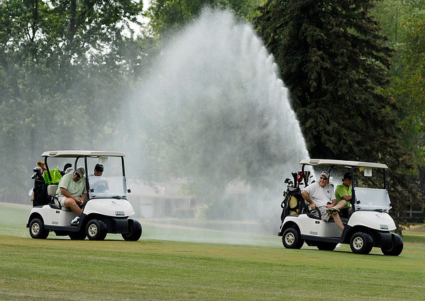 As these golfers were going to their assigned starting hole for the start of the annual Community Hospital Emergency Dept. golf outing Friday afternoon at The Edge they decided a way to keep cool on the hot day was to drive through the water spray from a fairway sprinkler.