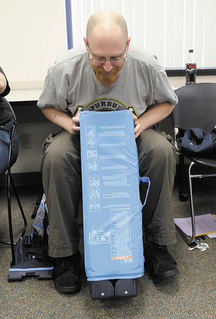 Bobby Pickell unpacks a portable playpen and basinet during a Safe Sleep Class at Community Hospital on Wednesday, June 13, 2012.