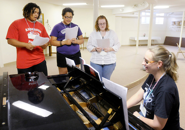 """From left, Darius Rhodes, Deanna Rhodes, Anna Custer and their instructor Lizz Schauf go over a piece of music during Central Christian Church's C.A.M.P. (Central Art, Music and Parables) on Monday. The CAMP meets from 5:45 to 8:30 p.m. Monday through Friday. This week's camp is for kids in 2nd through 12th grades and is still open to new campers. Next week's is for kids 4 years old through 1st grade. The camp culminates in a performance of Rick Vale's """"Play on Words"""" which is open to the public and will be performed on June 30th at 7 p.m. at Central Christian Church."""