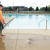 Southside Pool lifeguard Zach Sylvester hoses down the pool deck Monday in preparation for the opening of the swimming pool Tuesday.