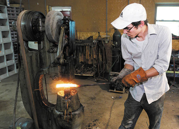 """Andrew Davis uses a power hammer as he forges a piece of pattern welded steel in his Middletown studio. A recent graduate from Ball State has been doing metalwork since he was a kid and created a sword for the movie """"Thor."""""""