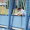 Benjamin Huff, of Anderson, tried his luck at fishing off the pedestrian bridge near Edgewater Park Monday evening to hit a spot in the middle of White River.