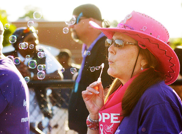 Connie Neal blows bubbles during the survivor lap during the Relay for Life at Highland Junior High School on Friday.