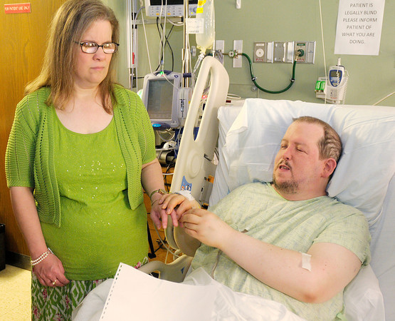 Kevin LaRose places a ring on the finger of his bride Sarah Blake as they are married at St. John's Hospital on Saturday. Sarah and Kevin decided not to let an unexpected illness postpone their nuptials.
