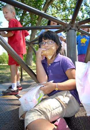 Veronica Magallanes, 7, enjoys her sack lunch from New Covenant Ministries while riding the merry-go-round at Meadowbrook Park Friday.
