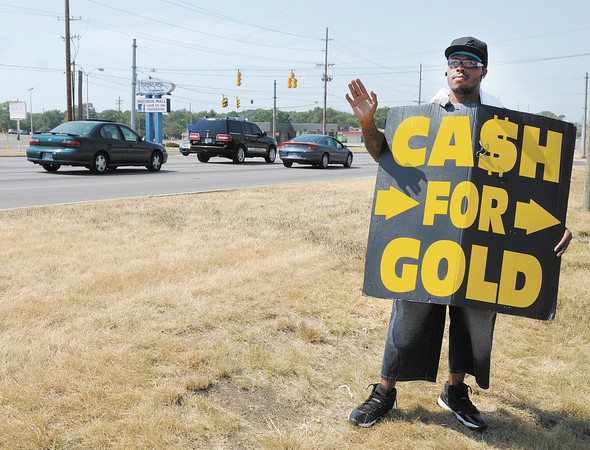 Darnell Warner waves to passing motorists as he wears a sandwich board advertising a Cash for Gold business in the shopping center across from Mounds Mall on Thursday afternoon. Warner said he wasn't bothered by Thursday's record temperatures but enjoys the hot weather.