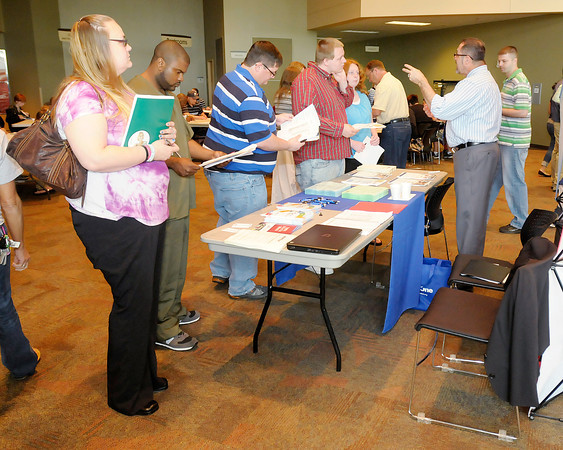 Job seekers line up at the Work One booth during the Central Indiana Job/Career Fair at Madison Park Church of God on Thursday.