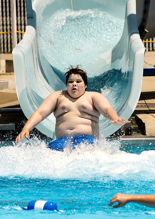 Dalton Parks, 14, of Pendleton, hits the water at the end of the water slide while swimming at Brown Pool in Pendleton Tuesday afternoon.