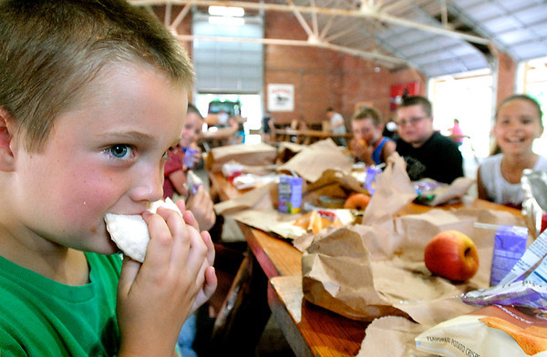 Matt Hood, 7, enjoys his Uncrustables peanut butter and jelly sandwich along with his Elwood YMCA day camp mates at the Elwood Community Schools summer lunch program at Callaway Park in Elwood.  The program provides a sack lunch to children under 18 that is enrolled in Elwood Community Schools.