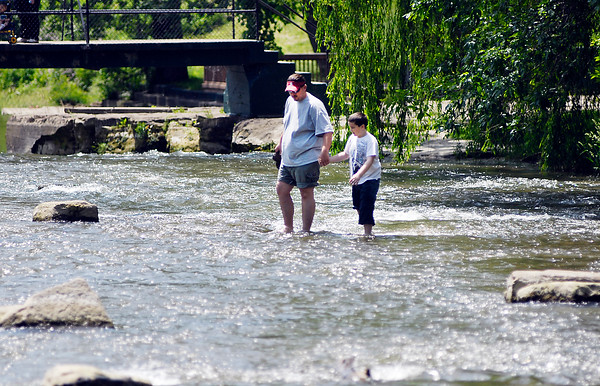 Steve Corbett walks through Fall Creek with his son Ayden, 9, as they scour the creek bed above the falls in Falls Park Tuesday afternoon.  The Corbetts,  from Elwood, were at the park on a family outing.
