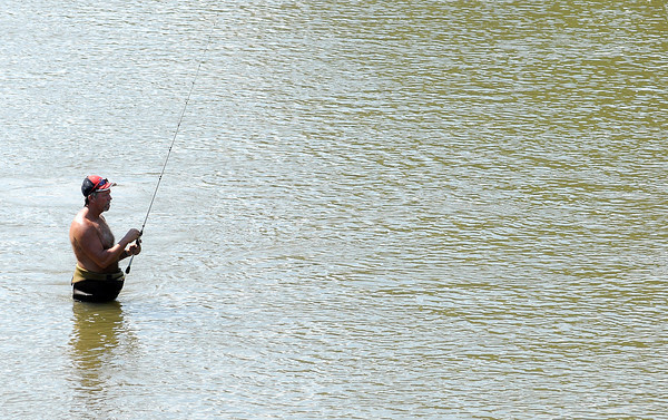 An angler wades into the White River in downtown Anderson as he tries his luck Tuesday afternoon.