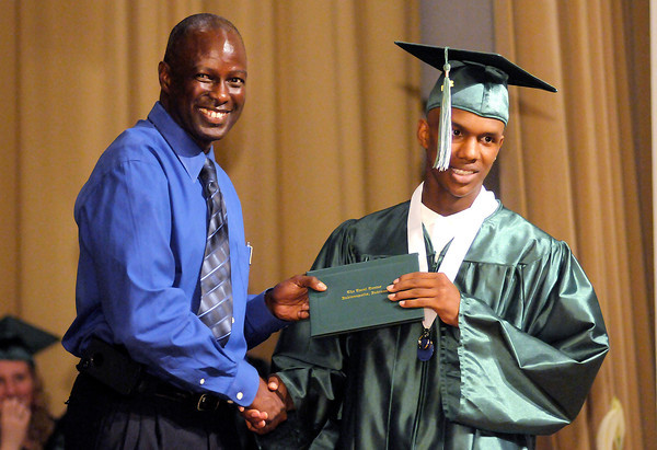 Rodney Chamberlain presents Da'Juan Johnson with his diploma during The Excel Center's graduation at the City Building auditorium on Thursday.