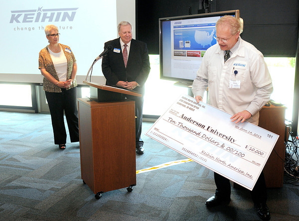 Greg Young, Vice President and Director of Keihin North America, presents Anderson University President James Edwards and Provost Marie Morris with a donation of $10,000 for AU's new engineering department during a dedication and ribbon cutting at Keihin's new location at the Flagship Enterprise Center in Anderson on Friday.<br /> Don Knight/The Herald Bulletin
