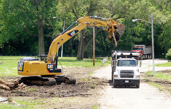 Don Knight/The Herald Bulletin<br /> A back hoe removes debris from trees removed at Edgewater Park as construction to improve the levee begins. According to the U.S. Army Corp of Engineers the project is expected to be completed by December 2014.