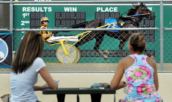 Ricky Macomber Jr., driving Earls Little Dude in the second race, goes by the grandstands and the fans Tuesday evening at Hoosier Park.