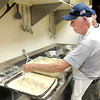 Bernie Bruns breads Alaskan Pollock during a fish fry at the Knights of Columbus in Anderson.