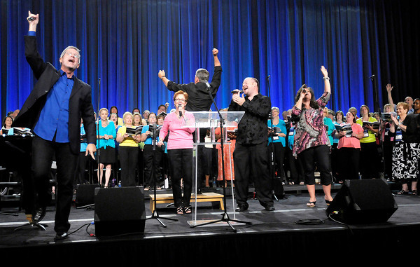 """Don Knight/The Herald Bulletin<br /> The worship team brings the crowd to their feet as they perform """"He Reigns"""" during the Opening Event of the Church of God Global Gathering at the Kardatzke Wellness Center on Saturday."""