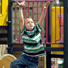 Six year old Aiden Porter keeps his eyes on his target as he swings on the rings at the Alexandria Pike playground at Shadyside Lake Monday afternoon.<br /> Aiden was at the park with his grandfather for a family outing on a warm, sunny afternoon.