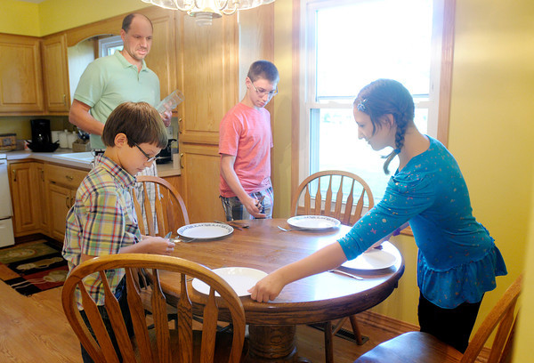 Scott Gull and his kids, from left, Jacob, Zachary and Makenna set the dinner table on Tuesday.<br /> Don Knight/The Herald Bulletin