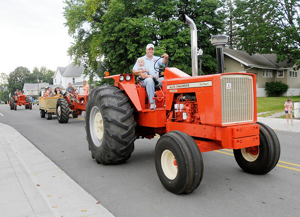 Don Knight/The Herald Bulletin<br /> Classic tractors drive down Main Street during the Summitville Country Fair Grand Parade on Wednesday. The fair continues through Saturday.